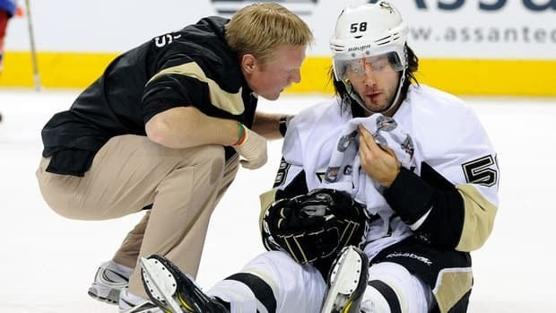 Kris Letang of the Pittsburgh Penguins is tended to by a trainer after being hit by Max Pacioretty of the Montreal Canadiens during the third period of Saturday's game. Letang left the game, but returned to score the overtime winner.