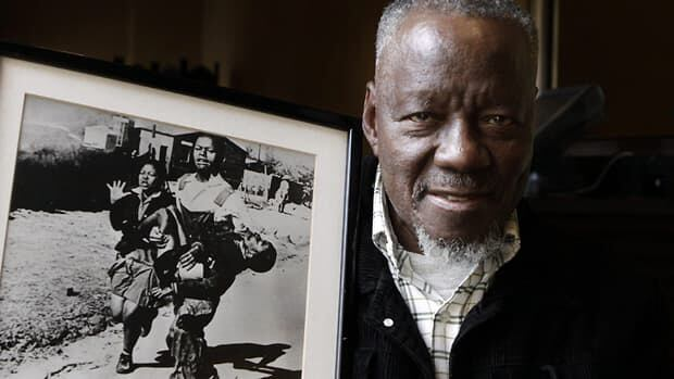 Sam Nzima poses with his iconic photo of Hector Pieterson, a 13-year-old fatally shot by police during the 1976 Soweto Uprising, in South Africa on Wednesday.