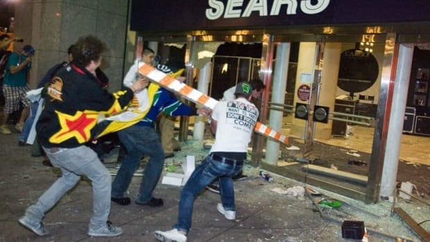 Rioters break the front doors of a Sears department store in downtown Vancouver. Social media groups are organizing to identify culprits.