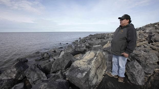 A man stands atop a beach barrier of small boulders in Tuktoyaktuk, N.W.T. His Arctic community is being threatened by sinking land due to thawing permafrost.