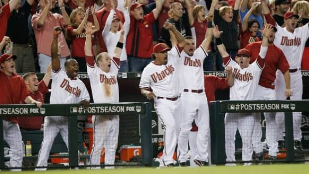 Players in the Arizona Diamondbacks' dugout erupt following a fifth-inning grand slam by Diamondbacks' Paul Goldschmidt in Game 3 on Tuesday in Phoenix.