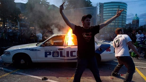 Vancouver Canucks fans pose in front of a burning police cruiser during a riot following game 7 of the NHL Stanley Cup final in downtown Vancouver on June 15.