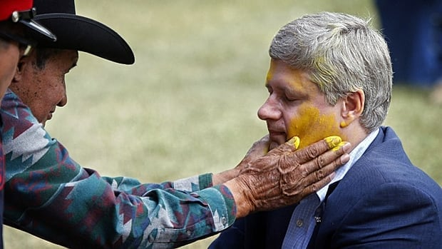 Prime Minister Stephen Harper has his face painted by Blood Tribe elder Pete Standing Alone while being made an honorary chief of the tribe during a ceremony in Stand Off, Alta., on Monday.