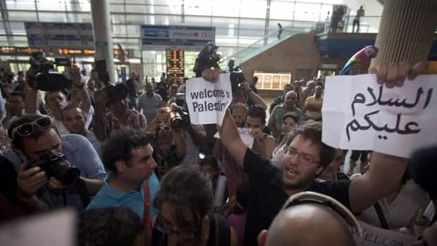 A pro-Palestinian activist holds a Welcome to Palestine sign at an airport near Tel Aviv, Israel Friday, July 8, 2011. Canada has since rejected Palestine's effort to win recognition at the United Nations as an independent state.