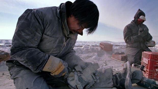 Sculptors work on soapstone near Iqaluit. A Montreal boutique that sells Inuit carvings and other aboriginal artworks ditched its payment terminal last year in favour of a new cloud-based system.