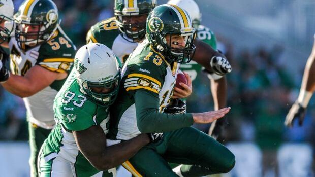 Saskatchewan Roughriders defensive tackle Tearrius George, left, takes down Edmonton Eskimos quarterback Mike Reilly.