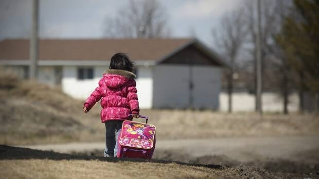 Autumn Alexander pulls her case to the evacuation centre to catch a bus to Winnipeg as her family is evacuated from the Roseau River First Nation, Man., on Sunday.