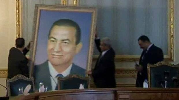 Officials remove a portrait of ousted Egyptian President Hosni Mubarak from the main Cabinet building in Cairo on April 21.