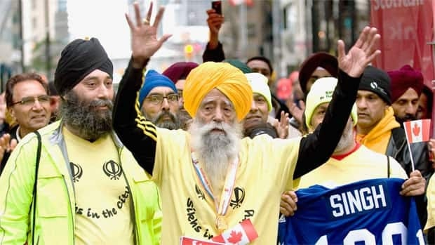 Fauja Singh, 100, raises his hands in celebration as he crosses the finish line in Sunday's Toronto waterfront marathon. Singh set a world record as the oldest person to complete a race of that distance.