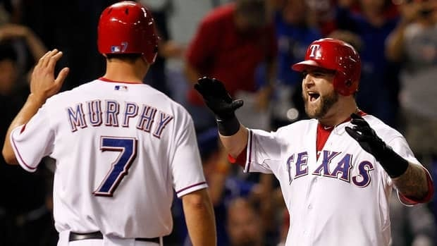 Mike Napoli, right, celebrates his three-run home run with teammate David Murphy in Game 4 of the World Series. The Rangers evened up the series with the Cardinals at two games a piece.