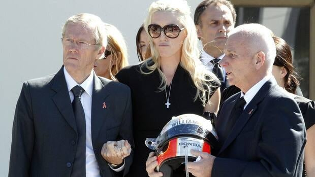 Clive Wheldon, right, father of IndyCar driver Dan Wheldon, holds his son's helmet as Dan's wife Susie, centre, and her father Sven Behm, left, watch as Wheldon's coffin is placed in a hearse after funeral services Saturday in Florida. Wheldon was killed last Sunday in a race at Las Vegas.