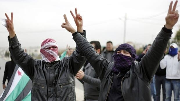 Masked Syrian refugees make victory signs at a protest in front of the Syrian embassy in Amman, Jordan on Dec. 30. The deal, signed in Egypt on Friday, says all Syrian citizens are equal and a new constitution should be drafted after the current regime has been ousted.