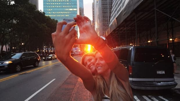 Pedestrians pose for a photo during Manhattan-henge. (Michael Loccisano/Getty)