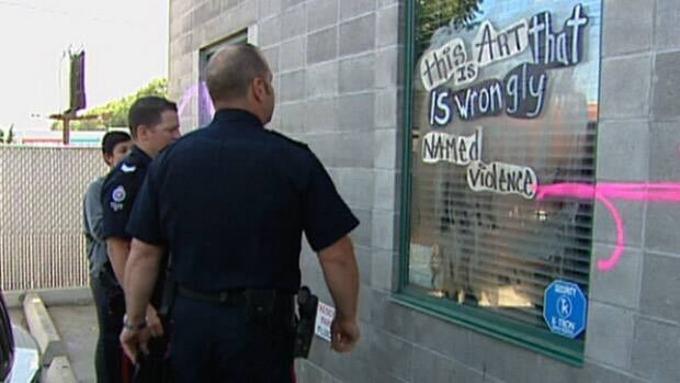 Edmonton Police examine vandalism on the exterior of Fluid Hair Salon.