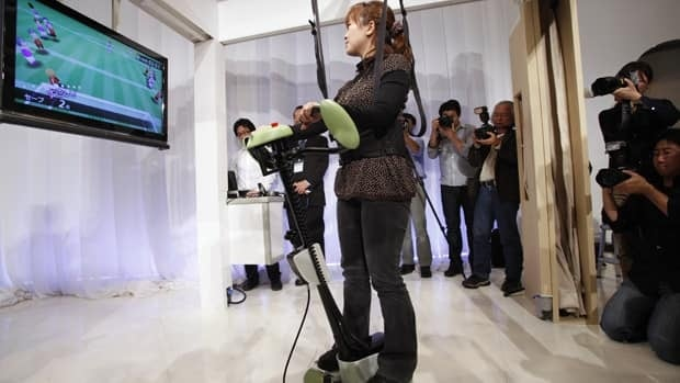 A woman standing on a two-wheeled balance training assist robot, developed for people with impaired balance, plays a computer during a news conference to showcase Toyota's new robots.