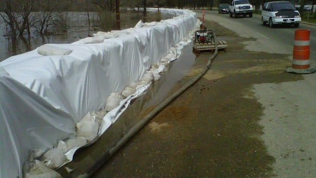 Officials in Brandon, Man., say dikes in their community will have to be raised to meet a higher than expected surge of water on the Assiniboine River.