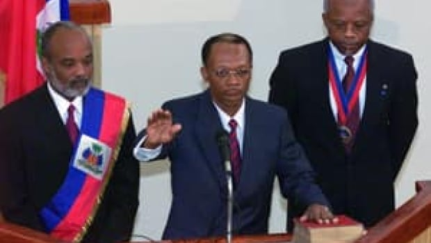 Jean-Bertrand Aristide is sworn in as Haiti's president for his second term, in front of departing president René Préval, left, and Senate president Yvon Neptune in Port-au-Prince on Feb. 7, 2001. Préval returned to the office in 2006.