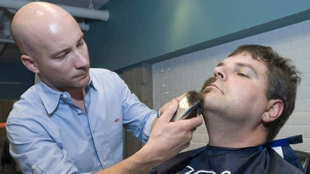 Judah Down of JD's Barber Shop gives Jason Purvis, 34, his first clean shave in 15 years on Oct. 28, 2009, in Vancouver as part of the Movember campaign.