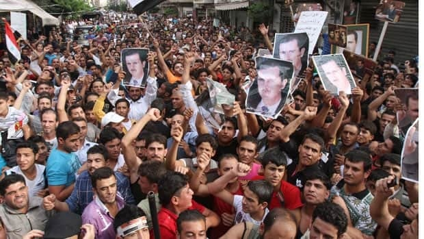 Syrian regime supporters carry pictures of President Bashar al-Assad during a protest in the Nabaa neighbourhood of Beirut on Sunday.