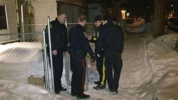 Officers take a man into custody after the Winnipeg police helicopter was targeted by a laser pen on Thursday morning.