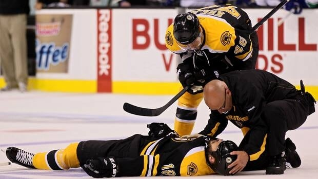 Bruins forward Nathan Horton (18) is helped by a trainer as teammate David Krecji looks on at TD Garden on Monday night.