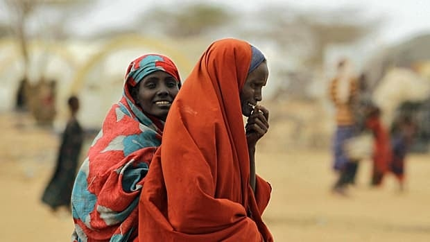 Recently-arrived Somali refugees walk amongst makeshift shelters on the outskirts of Dagahaley Camp, outside Dadaab, Kenya.