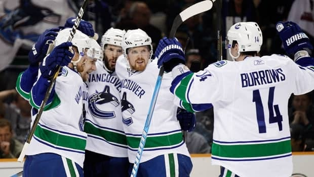 Vancouver Canucks centre Ryan Kesler is mobbed by teammates after his goal against the San Jose Sharks during the second period of Game 4 in San Jose on Sunday.