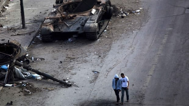 Men walk next to a destroyed tank in Tripoli Street, the centre of fighting between forces loyal to Libyan leader Moammar Gadhafi and rebels in downtown Misrata on May 23.