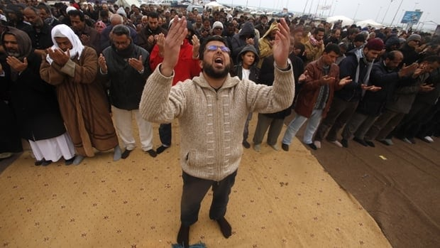 People in the Libyan city of Benghazi pray during a protest against leader Moammar Gadhafi on Tuesday.
