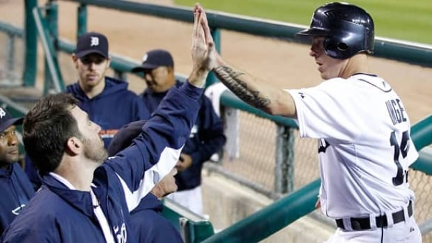 Brandon Inge, right, of the Detroit Tigers high-fives Justin Verlander, left, after scoring on a single by Ramon Santiago in the third inning against the New York Yankees. The Tigers won 5-4, and now lead the series by one game.