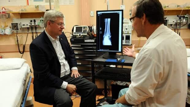 Prime Minister Stephen Harper talks with Dr. Jim Corkal at Stanton Hospital in Yellowknife before announcing $60 million over the next two years to improve health care in the North.