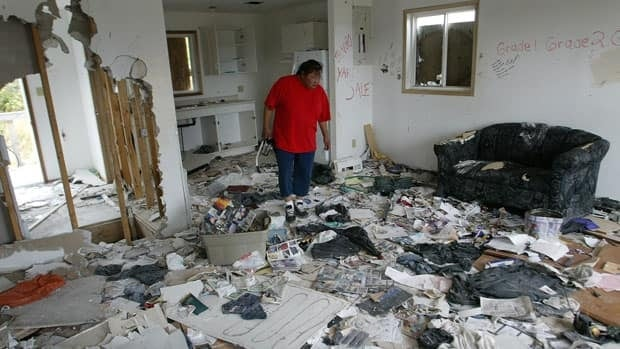 A substance abuse worker looks over a house used and vandalized by gas sniffers on Pauingassi First Nation Indian Reserve, near the Manitoba and Ontario border.