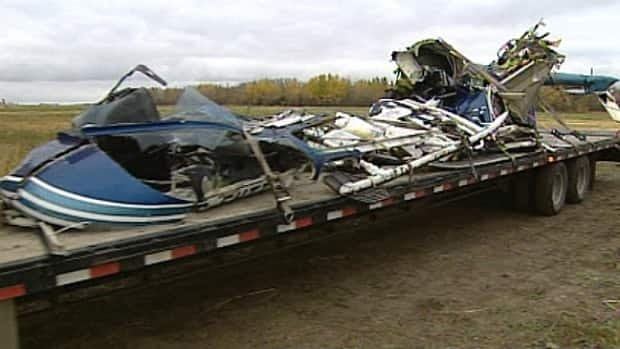 Crash investigators remove the wreckage of a helicopter that crashed near Drayton Valley, Alta. Wednesday. The pilot died when the helicopter crashed into a field one kilometre from the airport.