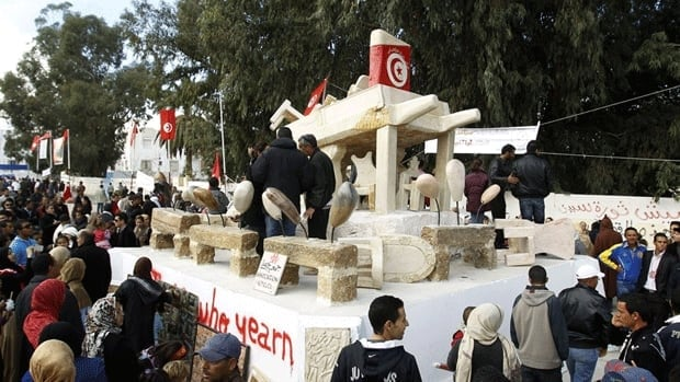 People walk past a statue depicting Tunisian produce seller Mohamed Bouazizi's cart, who set himself on fire last December in an act of protest that triggered the Arab Spring revolution.