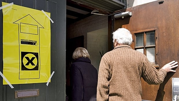 A man and a woman enter an advance polling station in Montreal on Friday.