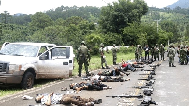 The bodies of gunmen laid out on a road beside their vehicle after a shootout with Mexican soldiers in the municipality of Tacambaro in the southern state of Michoacan on Aug. 16, 2011. The gunmen were suspected members of the Knights Templar, a splinter group that split from the La Familia Michoacan cartel, whose turf fight with the Los Zetas cartel is what spurred the start of President Felipe Calderon's crackdown against the cartels in 2006.
