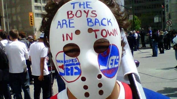 A Winnipeg hockey fan wears a painted goalie mask as he celebrates Winnipeg's NHL news on May 31.
