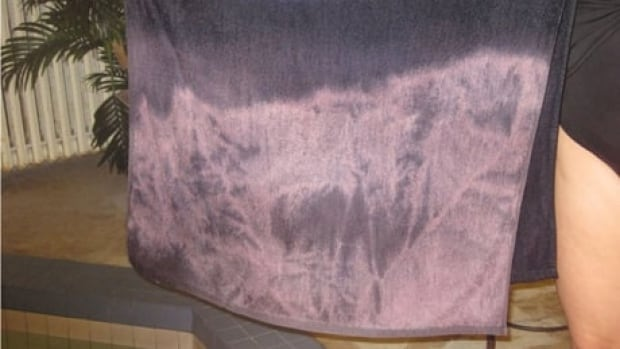 This towel changed colours after it was dipped in a hot tub at the spa in St. John's, according to a woman who says she received chemical burns there.