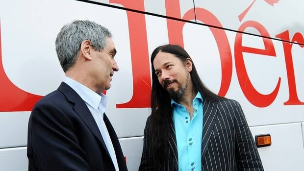 Liberal Leader Michael Ignatieff, left, shakes hands with Tragically Hip lead guitarist Rob Baker after a campaign stop at a science lab in Kingston, Ont., on Monday.