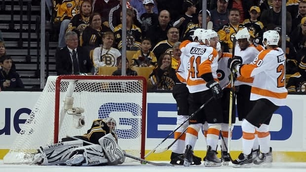 Claude Giroux (28) of the Philadelphia Flyers is congratulated by teammates after he scored in the first period as Boston's Tim Thomas, left, looks on helplessly.