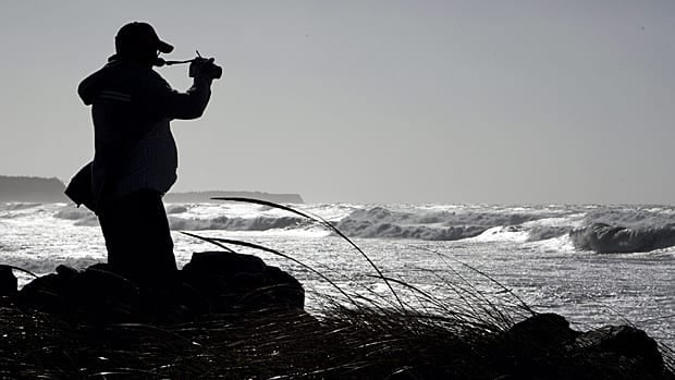 An unidentified man takes photos of the waves at Lawrencetown Beach near Halifax on Monday. The remnants of hurricane Irene buffeted the province with high winds and rain