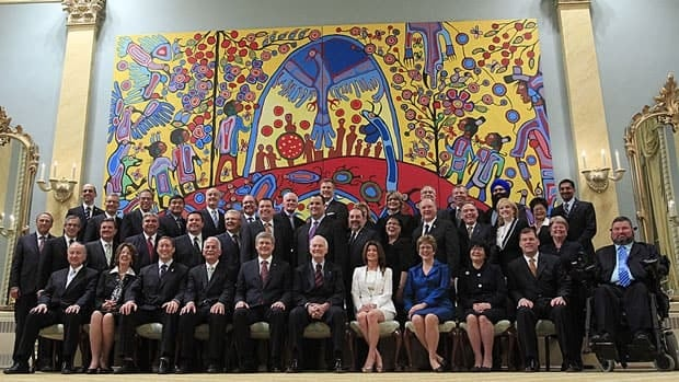 Prime Minister Stephen Harper sits with Gov. Gen. David Johnston, front row centre, and members of the federal cabinet following a swearing-in ceremony at Rideau Hall, May 18, 2011.