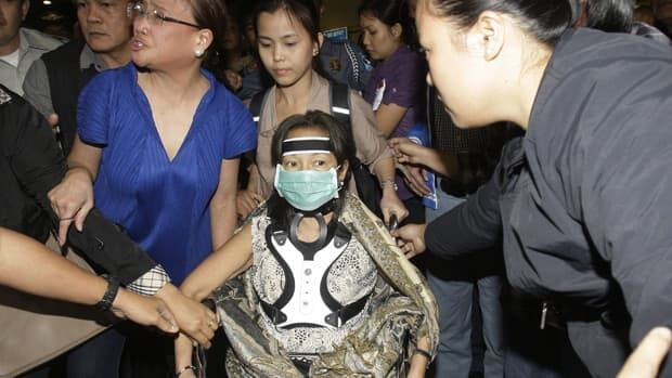 Former Philippine president and current member of Congress Gloria Macapagal Arroyo, centre , is assisted by her aides as they leave the airport in Manila, Philippines, Tuesday, Nov. 15, 2011. The Philippine government blocked Arroyo and her husband from leaving the country on Tuesday.