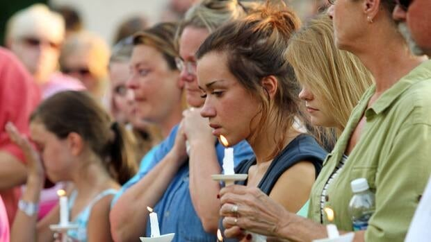 Members of the Copley, Ohio, community hold a candlelight vigil in honour of seven neighbors who were killed Sunday.