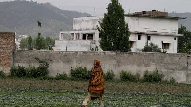 A woman walks by a house where al-Qaeda leader Osama bin Laden was caught and killed in Abbottabad, Pakistan.