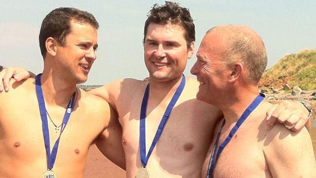 Todd McDonald, 36, Chris Dobbin, 37, and Peter McCormick, 53, celebrate after finishing a 13-kilometre swim across the Northumberland Strait on Sunday.