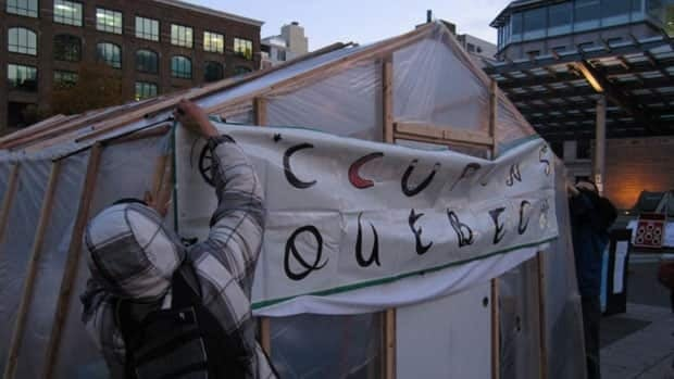 Protesters adjust a plastic cover on one of their makeshift shelters part of the Quebec Occupy encampment.