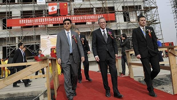 Minister of Natural Resources Joe Oliver, centre, visits a wood-frame apartment building in Tianjin, China, Nov. 7, 2011. Oliver is in China to promote Canada's oil and forestry industries.