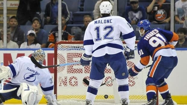 Islanders forward John Tavares, right, scores his second goal of the game as Lightning goalie Dwayne Roloson, left, and winger Ryan Malone look on.