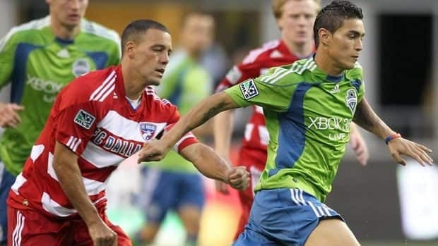 Miguel Montano, right, seen with the Seattle Sounders dribbles against Ugo Ihemelu FC Dallas in July 2010. Seattle loaned Montano to Montreal in August and on Wednesday, the Impact announced he would stick with the club for its inaugural MLS season.